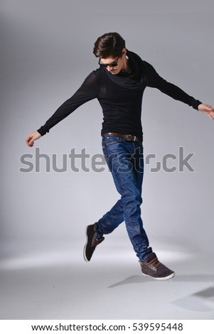 full length photo of a young casual man in jeans with sunglasses jumping posing-light background