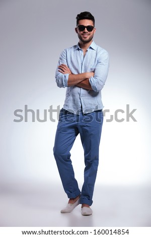 full length photo of a young casual man with his hands folded, looking into the camera and smiling.on gray background - stock photo