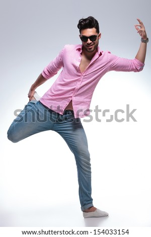 full length photo of a young fashion man posing with his foot in his hand. on a white background