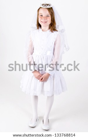 Full length photo of a young girl smiling in her First Communion Dress and Veil and white shoes
