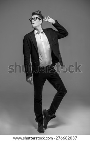 Full length photo of an elegant young fashion man in tuxedo and jeans. Black and white fashion shot.
