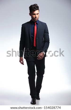 full length photo of an elegant young fashion man in tuxedo walking forward and looking away from the camera. on gray background - stock photo