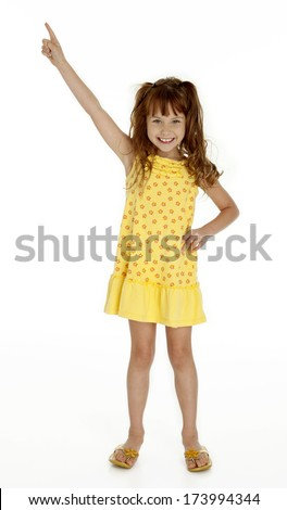 Full length photo of cute little girl pointing upward on white background - stock photo