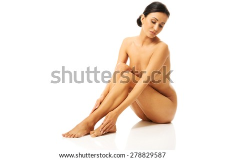 Full length photo of nude woman sitting on the floor and looking down.