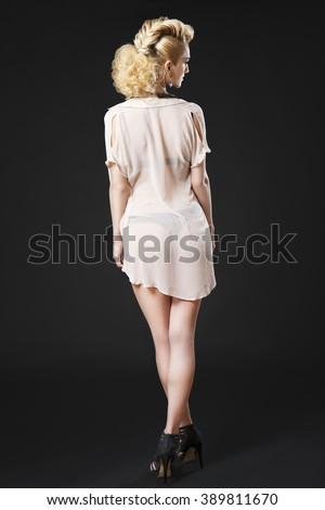 Full length photo of tall attractive blonde girl posing in lingerie, wearing high heels and see through shirt on black background - stock photo