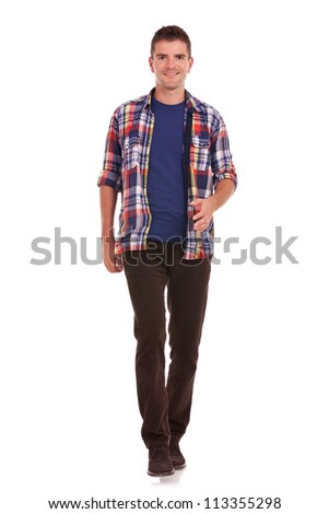 full length picture of a casual friendly young man walking towards the camera �¢?? isolated over a white background - stock photo