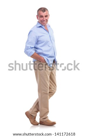 full length picture of a casual senior man posing with his hands in his pockets and a smile on his face. isolated on white background