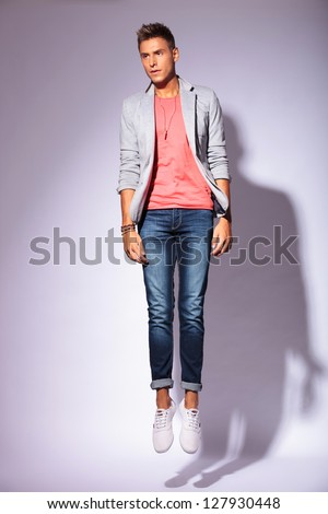 full length picture of a casual young man jumping with his feet close together, looking away from the camera. on light background with shadow - stock photo