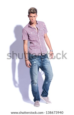 full length picture of a casual young man looking at the camera with a serious expression. on  white background with hard shadow - stock photo