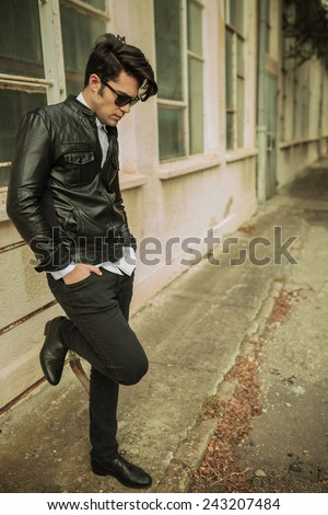 Full length picture of a casual young man looking down while leaning on a ladder, near old building. - stock photo