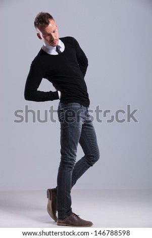 full length picture of a casual young man posing with his hands at his back while looking down. on gray studio background