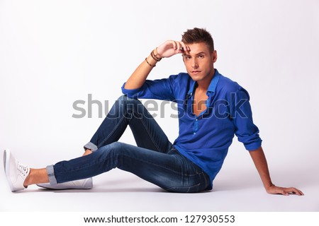 full length picture of a casual young man sitting on the floor and looking pensively at the camera, on gray background