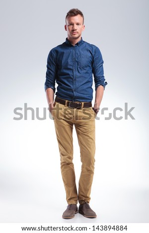full length picture of a casual young man standing with his hands in his pockets while looking into the camera with a serious expression. on gray background - stock photo