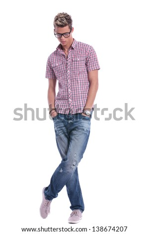 full length picture of a casual young man standing with his hands in his pockets, with his legs crossed, while looking down . on background