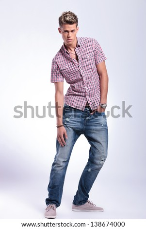 full length picture of a casual young man touching his leg with a hand and holding the other one in his pocket while looking at the camera. on background