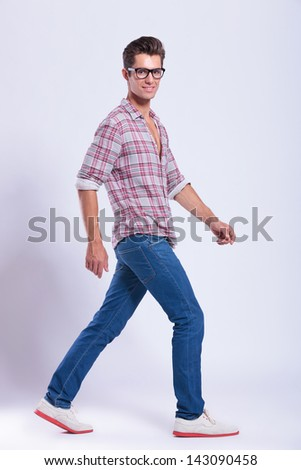 full length picture of a casual young man walking away from the camera and looking at you with a smile. on gray background - stock photo