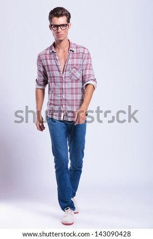 full length picture of a casual young man walking towards the camera wit a serious expression. on gray background - stock photo