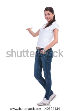 full length picture of a casual young woman presenting something in her back with a hand in her pocket and smiling at the camera. isolated on white background - stock photo