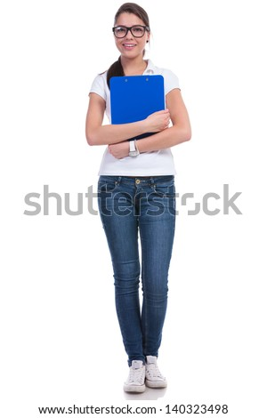 full length picture of a casual young woman standing with a clipboard at her chest. isolated on white background