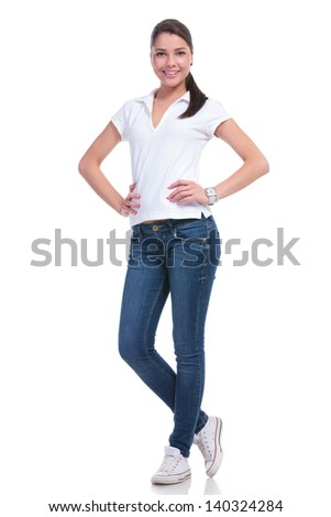 full length picture of a casual young woman standing with her hands on her hips and smiling to the camera. isolated on white background - stock photo