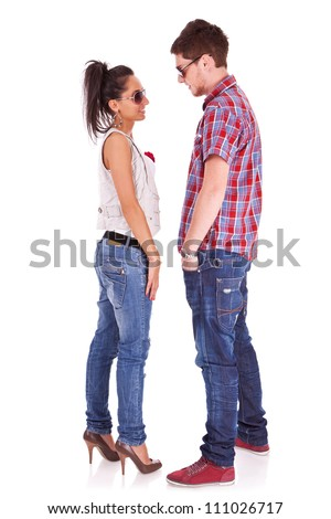 Full length picture of a cute couple standing face to face , looking at each other over white background