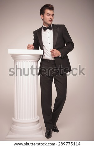 Full length picture of a elegant business man looking away while pulling his jacket. - stock photo