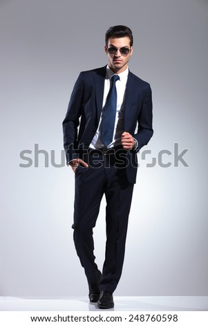 Full length picture of a elegant business man posing on grey studio background, holding one hand in his pocket while pulling his jacket. - stock photo