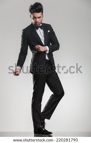 Full length picture of a elegant handsome man snapping his fingers while looking at the camera. - stock photo