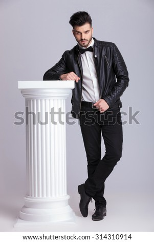 Full length picture of a handsome young business man looking at the camera while leaning on a white column. - stock photo