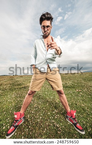 Full length picture of a handsome young man standing with his legs apart, holding one hand in his pocket while pointing at you. - stock photo