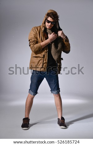 full length picture of a serious young casual man in short jeans with scarf posing in studio