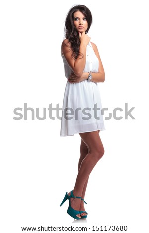 full length picture of a young beautiful woman touching her chin and looking away from the camera. isolated on a white background - stock photo