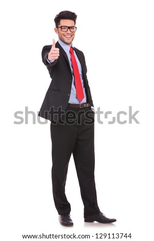 full length picture of a young business man showing thumb up and holding the other hand in his pocket, while smiling to the camera  on white background - stock photo