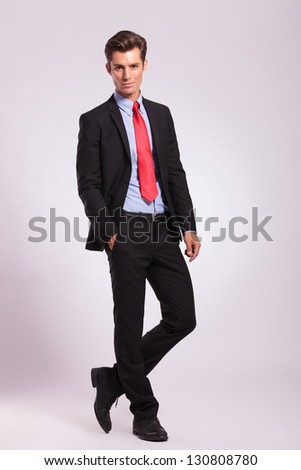 full length picture of a young business man standing with a hand in his pocket, legs crossed, and looking into the camera, on a gray background - stock photo