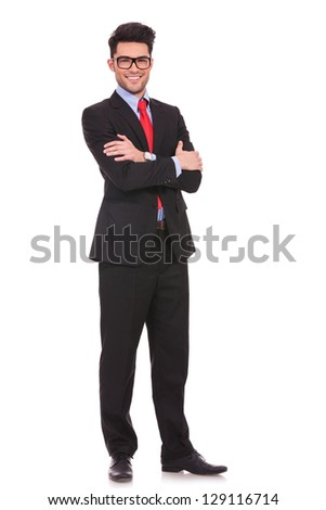 full length picture of a young business man standing with his hands folded and smiling to the camera on white background - stock photo