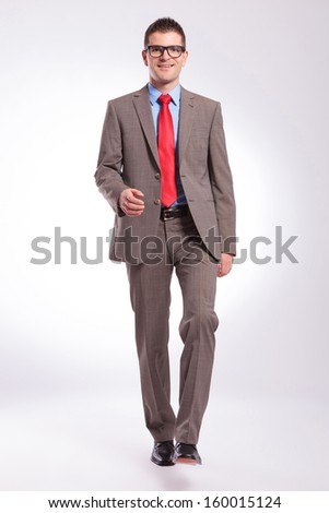 full length picture of a young business man walking toward camera with a smile on his face. on a gray background