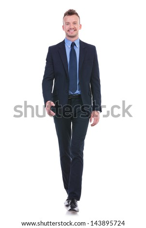 full length picture of a young business man walking towards the camera with a smile on his face. on white background - stock photo