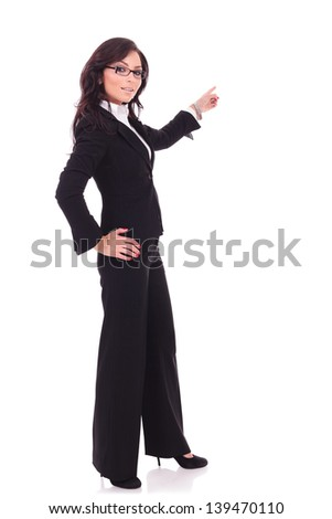 full length picture of a young business woman pointing to her back and holding the other hand on her hip, while looking at the camera. on white background
