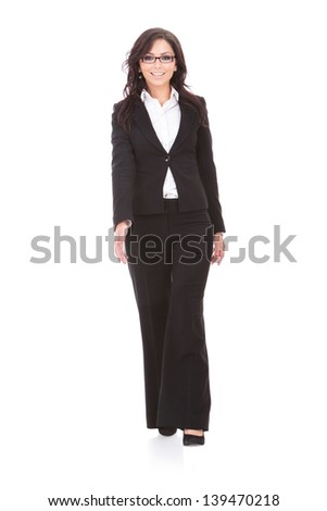 full length picture of a young business woman walking towards the camera and smiling. on white background