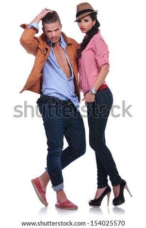 full length picture of a young casual couple looking at the camera while the man fixes his hair. on white background
