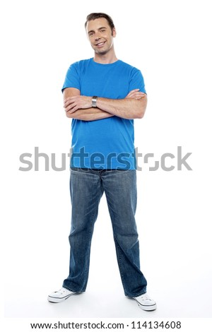 Full length picture of a young casual man. Arms folded and smiling - stock photo
