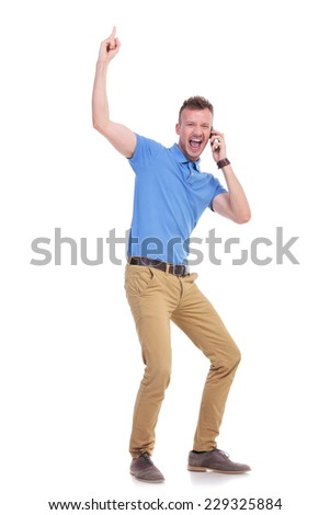 full length picture of a young casual man cheering over the phone while pointing upward and smiling for the camera . isolated on a white background - stock photo