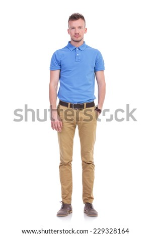 full length picture of a young casual man holding a hand in his pocket and looking into the camera with a serious expression. isolated on a white background - stock photo