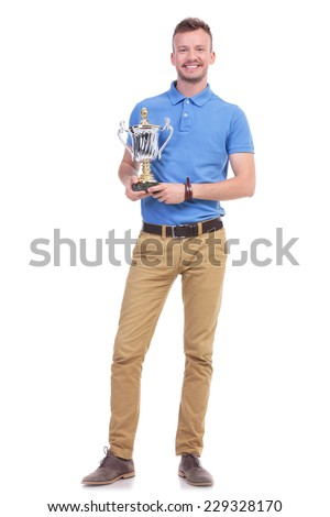 full length picture of a young casual man holding a trophy and smiling for the camera. isolated on a white background - stock photo