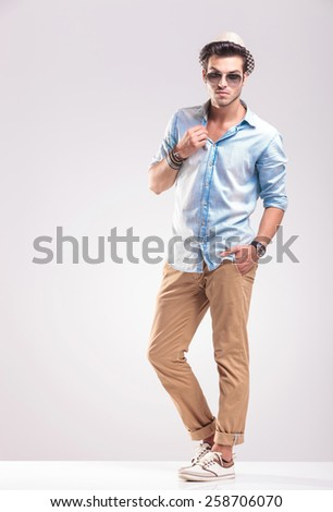 Full length picture of a young casual man posing on grey studio backgroud, holding one hand in his pocket while fixing his collar. - stock photo