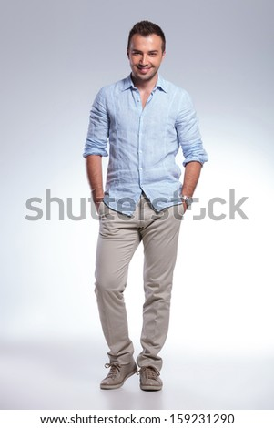 full length picture of a young casual man standing with both hands in pockets and smiling for the camera. on gray background - stock photo