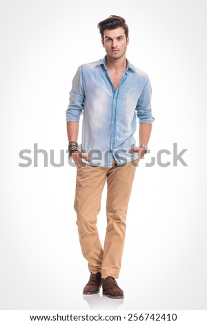 Full length picture of a young fashion man standing on studio background holding both hands in his pocket. - stock photo