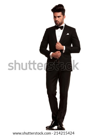 full length picture of an elegant young fashion man adjusting his tuxedo while looking to his side, away from the camera. on white background
