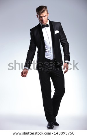full length picture of an elegant young fashion man in tuxedo posing, while looking at the camera. on gray background - stock photo