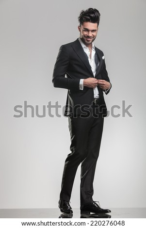 Full length picture of an elegant young man in tuxedo, smiling for the camera while closing his jacket.  - stock photo